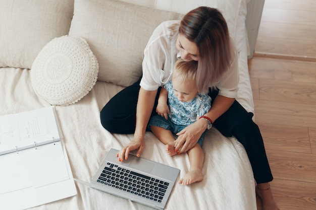 Modern woman working with child. multi-tasking, freelance and motherhood concept Free Photo