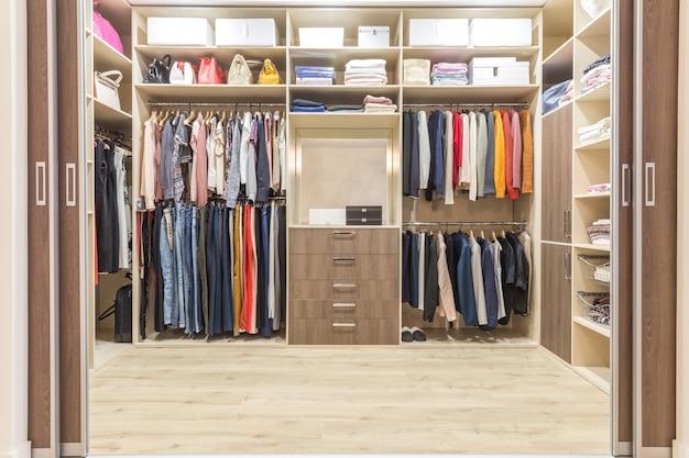 Modern wooden wardrobe with clothes hanging on rail in walk in closet design interior Premium Photo