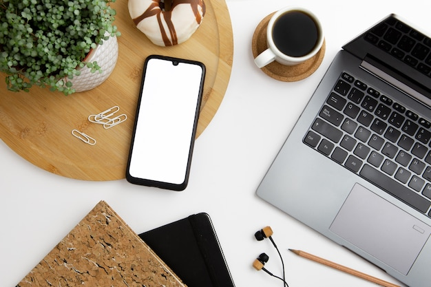 Modern workplace arrangement with phone and laptop Free Photo