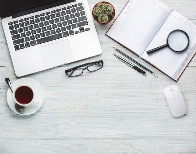 Modern workplace on wooden table with a lot of things on it Premium Photo