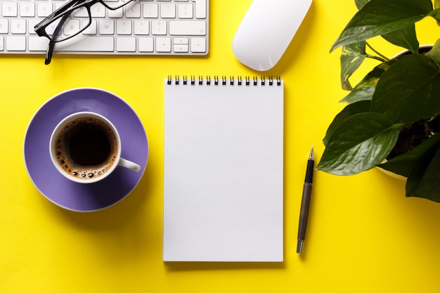 Modern yellow office desk table with keyboard notepad pen