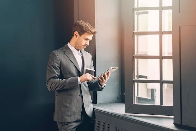 Современный молодой бизнесмен, проведение чашку кофе с помощью цифрового планшета Premium Фотографии