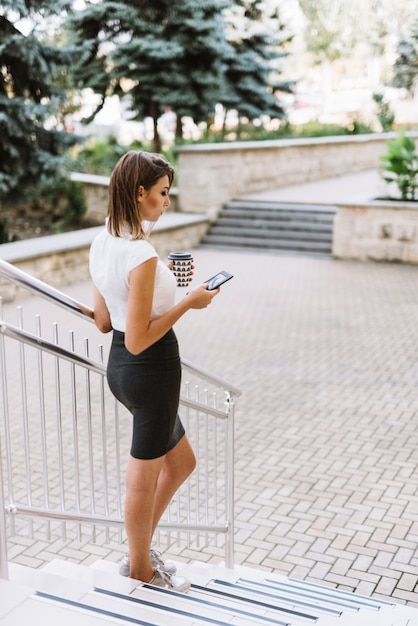 Modern young businesswoman standing on steps near the campus using smartphone Free Photo