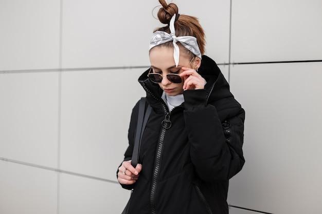 흰색 건물 근처 포즈 세련 된 선글라스에 니트 골프에 세련 된 배낭과 세련 된 블랙 재킷에 두건에 세련 된 헤어 스타일으로 현대 젊은 Hipster 여자. 패션 소녀. 프리미엄 사진