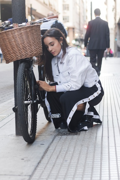 Modern young woman looking at her bicycle on street Free Photo