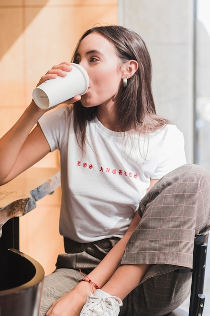Modern young woman sitting in cafe drinking the coffee Free Photo