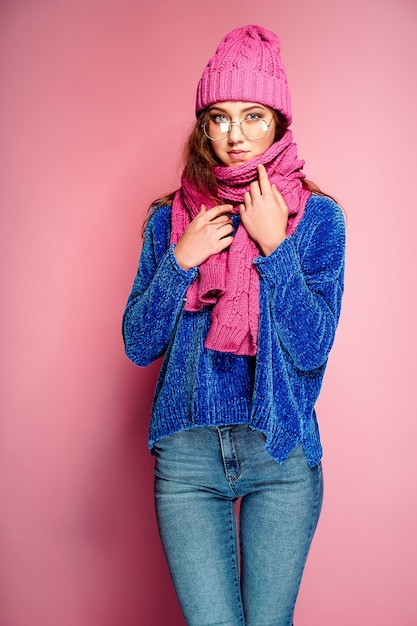 Modern young woman wearing blue sweater and pink hat, and scarf posing, making funny facial expression. Premium Photo