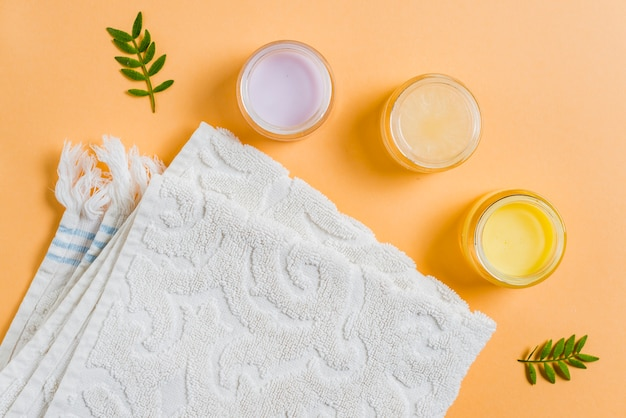 Moisturizer cream with white towel on colored background Free Photo
