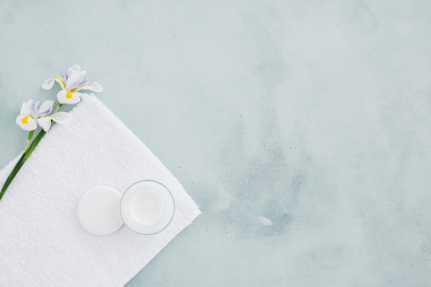 Moisturizing cream and flower on towel with copy space Free Photo