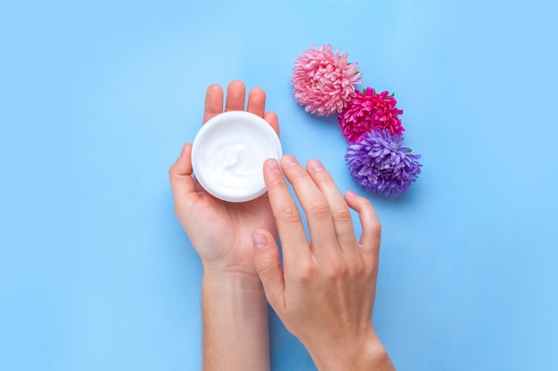 Moisturizing hand cream and flowers. hand care. elimination of dry skin of the hands. Premium Photo