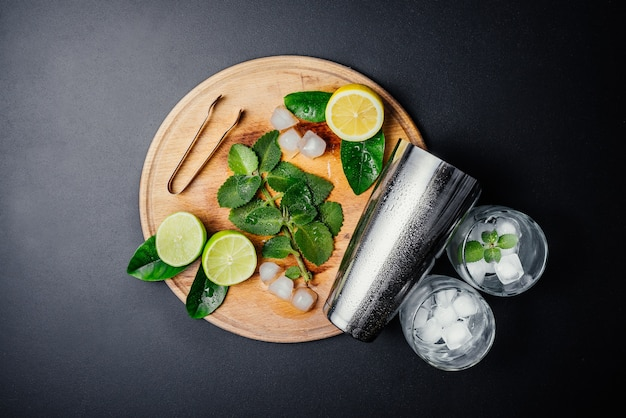 Mojito cocktail making. mint, lime, lemon, ice ingredients and bar utensils. Free Photo
