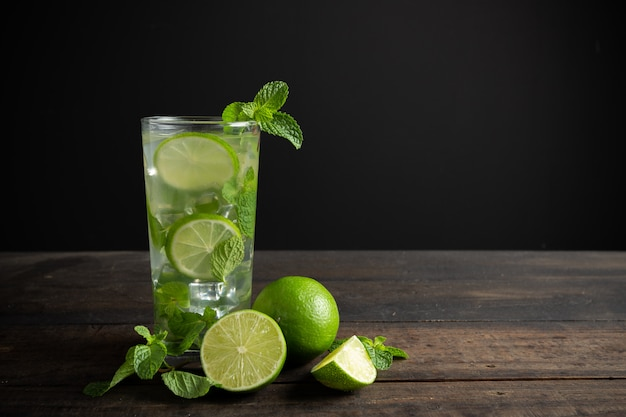 Mojito drink with lime, lemon and mint on wood table. Free Photo