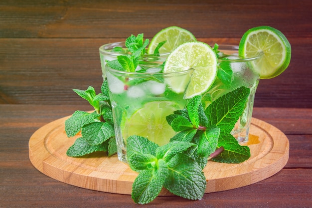 Mojito with mint and lime in a glass and a jug on the round board. brown wood background. Premium Photo
