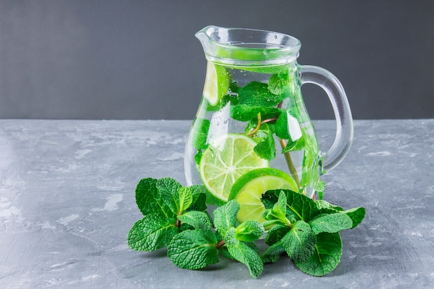 Mojito with mint and lime in a glass and a jug with tubes. grey marble background. Premium Photo