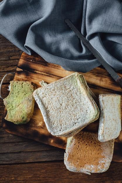 Moldy bread on wooden table Premium Photo