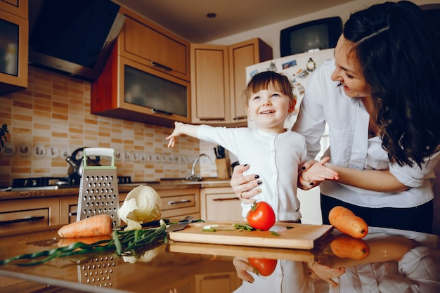 Mom along with her daughter cooks vegetables at home in the kitchen Free Photo