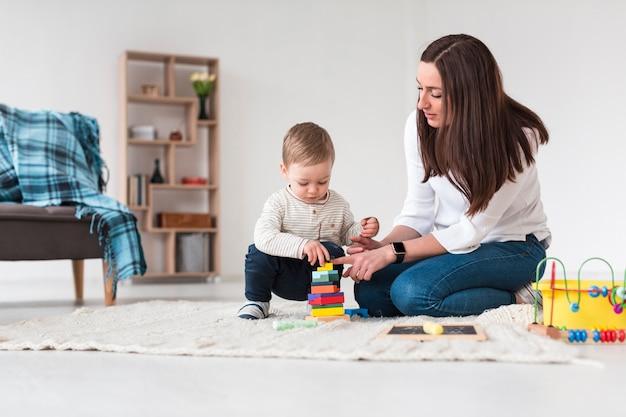 Мама и ребенок играют дома Premium Фотографии