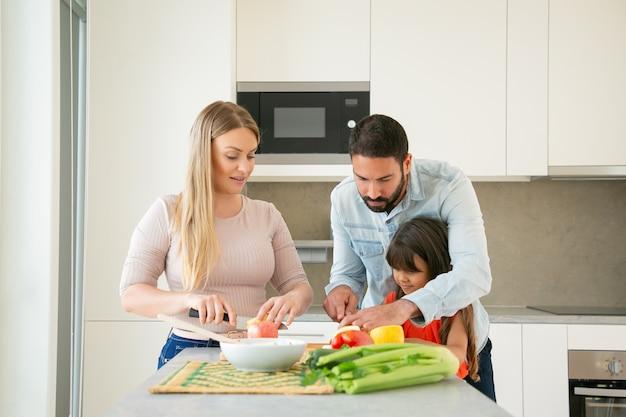 Мама и папа учат ребенка готовить. молодая пара и их девушка режут свежие фрукты и овощи для салата на кухонном столе. концепция здорового питания или образа жизни Бесплатные Фотографии
