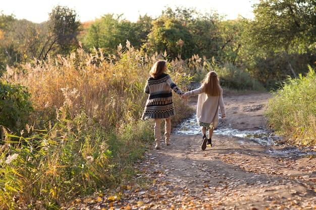 ママと娘は日没で歩いています。自然 Premium写真