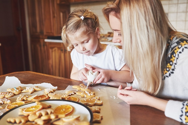 ママと娘は白い砂糖でクリスマスクッキーを飾る 無料写真