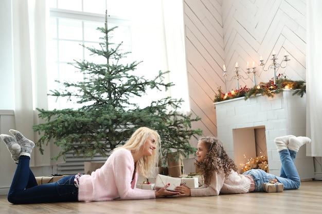 クリスマスに装飾されたリビングルームでの母と娘 無料写真