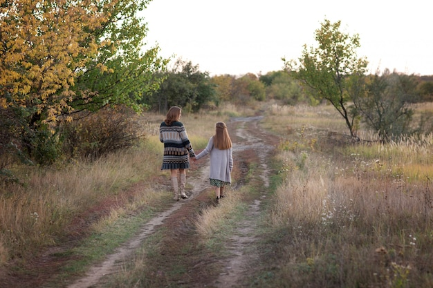 ママと娘は牧草地を歩く Premium写真