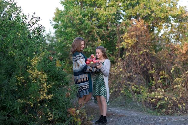 ママと娘が摘みりんごの上を歩く Premium写真
