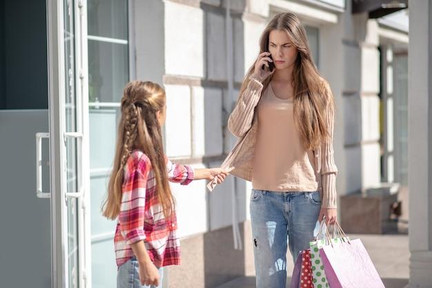 ショッピングバッグを持って通りを歩いているママと娘 Premium写真