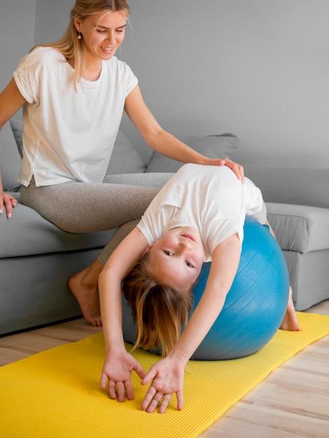 Мама и девушка тренируются на мяче дома Бесплатные Фотографии