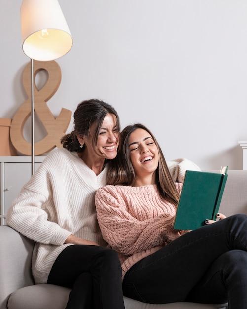 Мама и девушка на диване чтении Бесплатные Фотографии