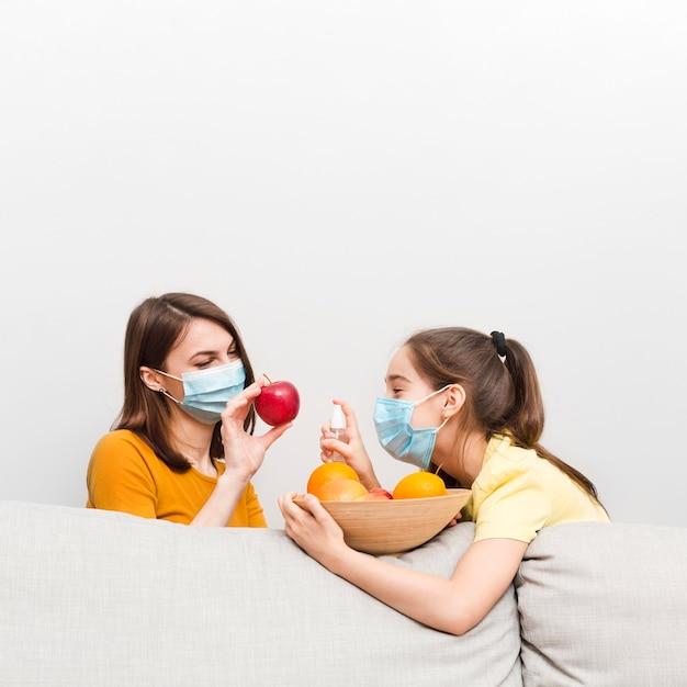 ママと自宅でマスクと果物を持つ少女 無料写真