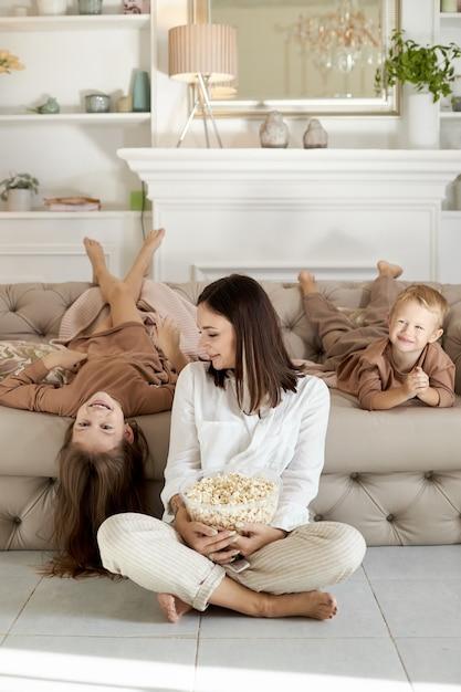 ママと子供たちは休日に家でポップコーンを食べます Premium写真