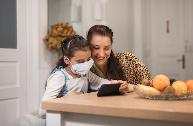 スマートフォンを使用しているママと小さな娘は、インターネットでオンラインビデオクリップを見て時間を過ごし、お気に入りの音楽、アプリ、現代の技術ユーザー、そして子供と一緒に家での活動を楽しんでいます。 Premium写真