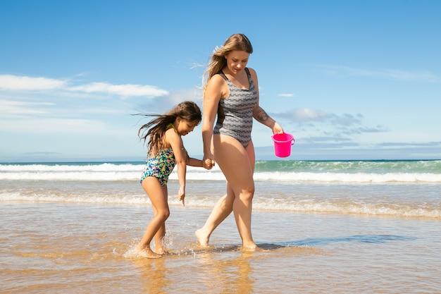 Мама и маленькая девочка гуляют по щиколотку в морской воде и мокром песке, собирая ракушки в ведро Бесплатные Фотографии