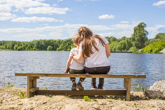 Мама и сын обнимаются, сидя на скамейке на берегу реки Premium Фотографии