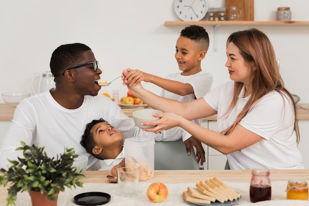 Мама и сын кормят отца едой Бесплатные Фотографии
