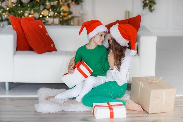 Мама и сын в новогодних нарядах и в хорошем настроении позируют перед камерой в новогодний день Premium Фотографии