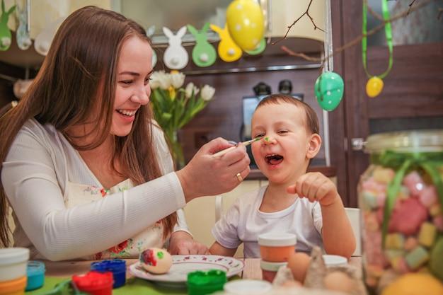 부활절 달걀 그림의 과정에서 엄마와 아들 집에서 장식 된 부엌에서 페인트로 바보 프리미엄 사진