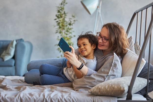 電話でビデオリンクを介して話しているママと息子 Premium写真