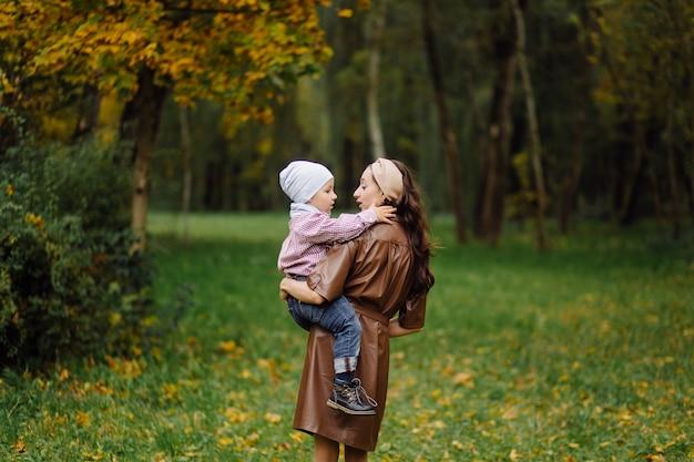 秋の公園で一緒に歩いて楽しんでいるママと息子。 無料写真