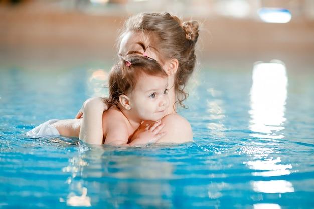 Mom and baby swim in the pool. Premium Photo
