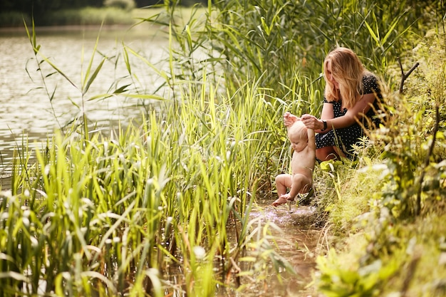 Mom bathes her little son in a river among tall green grass Free Photo