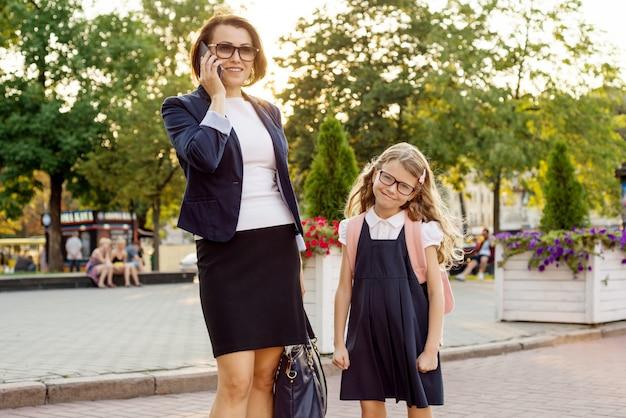 Mom businesswoman takes the child to school. Premium Photo