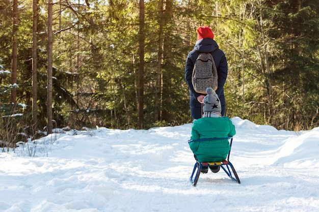 Mom carries her son on a sled through the snow-covered coniferous forest. Premium Photo