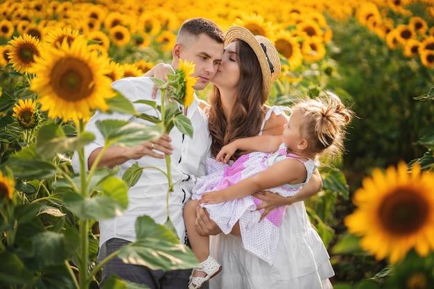 ママ、パパ、女の子の幼児がフィールドを歩きます。外で、休暇で、屋外で一緒に時間を過ごす幸せな若い家族。家族の休日のコンセプトです。 Premium写真