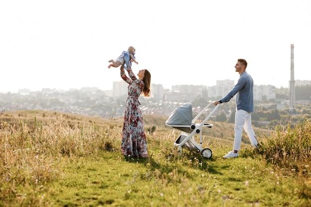 Мама, папа и маленькая женщина, весело на открытом воздухе в траве в летний день. день матери, отца и ребенка. счастливая семья на прогулке с столлер за городом. Premium Фотографии