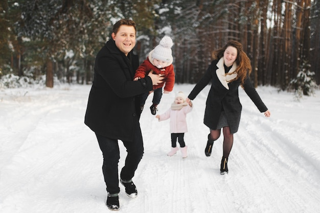 Mom, dad, daughter and little son having fun in the winter forest. active parents with children run in the snowy forest Premium Photo