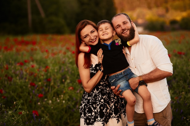 Mom and dad hold their little son on the arms standing on the green field with poppies Free Photo