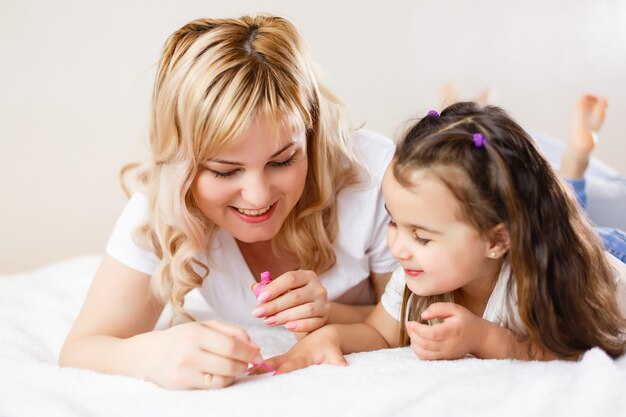 Mom and daughter in the bedroom on the bed in the curlers make up Premium Photo