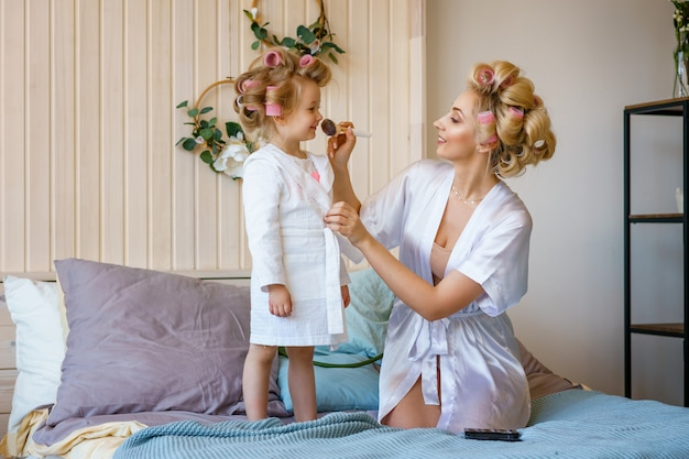 Mom and daughter in curlers , make a make-up to each other, a happy family Premium Photo